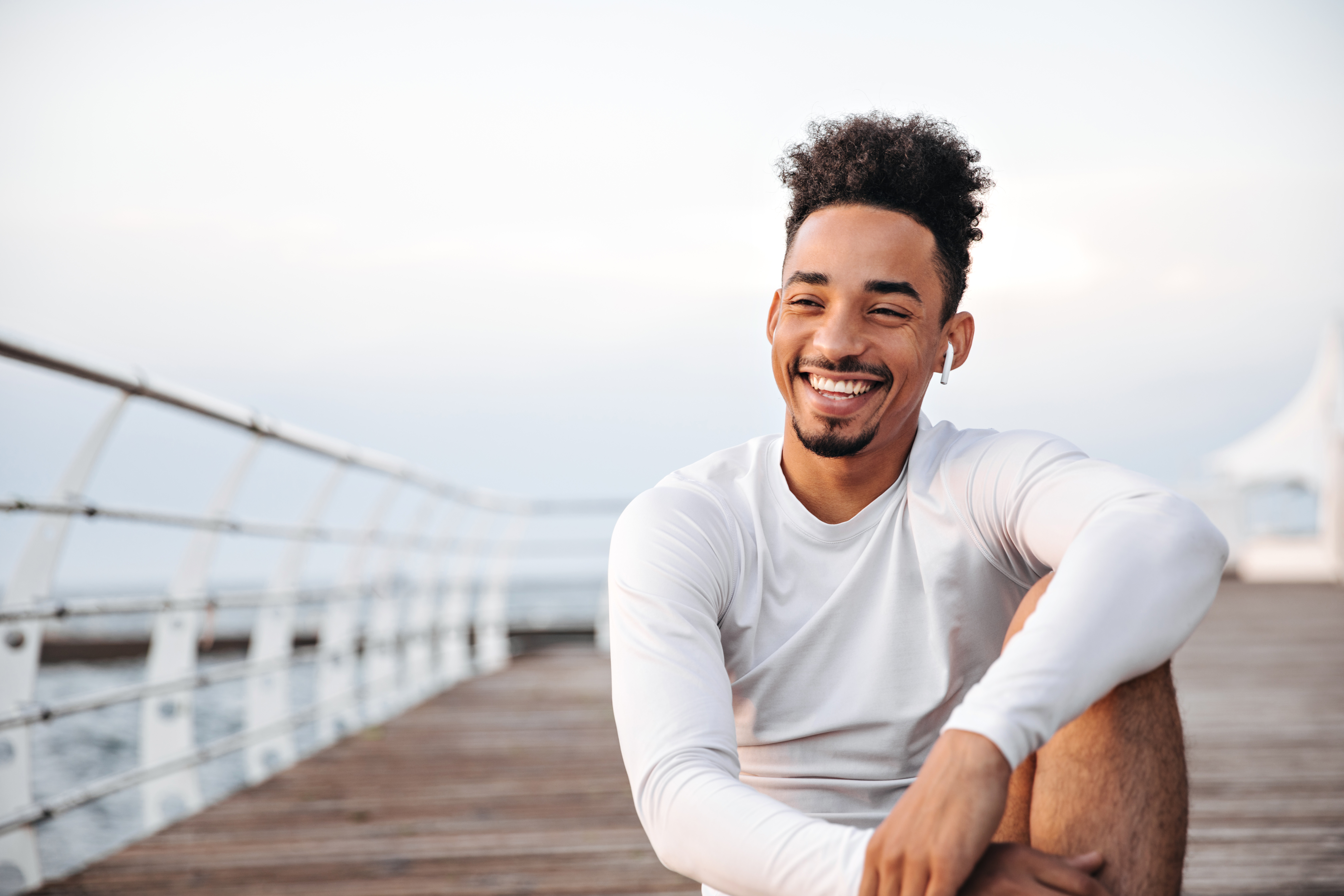 cheerful-curly-dark-skinned-man-white-long-sleeved-t-shirt-smiles-sincerely-rests-near-sea